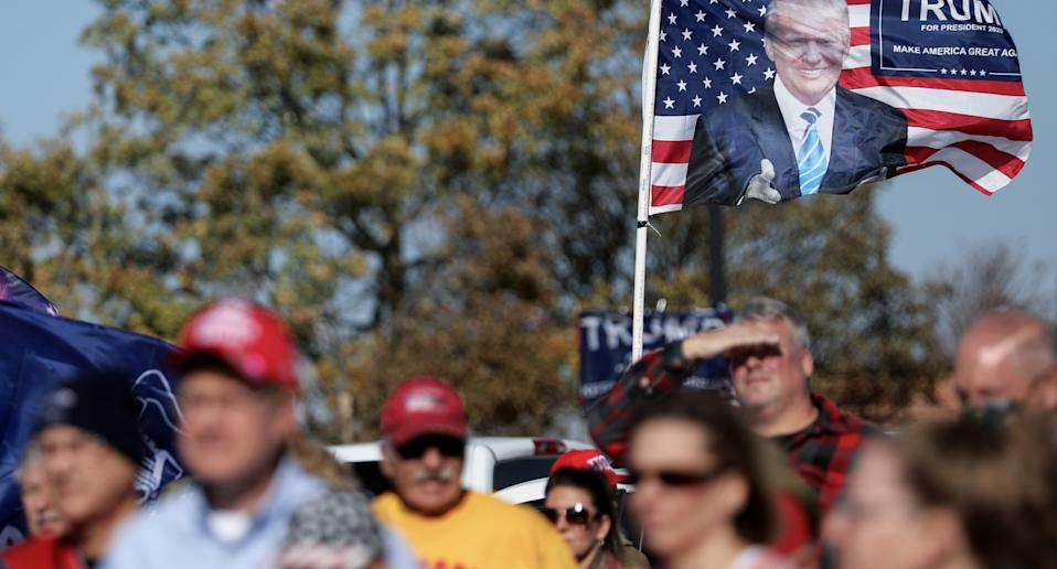 Trump supports shown marching with Trump hats and a flag.
