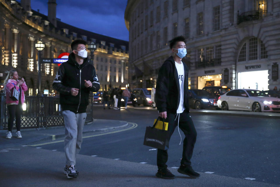 """Two pedestrians cross the street wearing masks in Piccadilly Circus, London, Saturday, March 14, 2020. British Prime Minister Boris Johnson has described the worldwide pandemic as """"the worst public health crisis for a generation."""" (Hollie Adams/PA via AP)"""