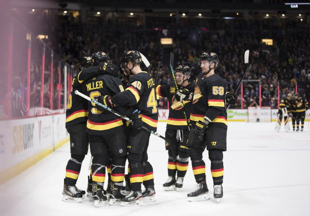 Vancouver Canucks' J.T. Miller (9) is mobbed by his teammates after scoring the winning goal against the Buffalo Sabres during overtime of an NHL hockey game in Vancouver, British Columbia, Saturday, Dec. 7, 2019. (Darryl Dyck/The Canadian Press via AP)