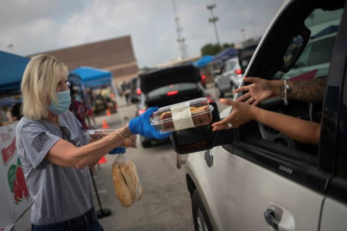 Volunteer give food to residents economically affected by COVID 19 pandemic during San Antonio Food Bank distribution in Texas