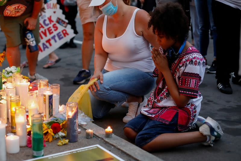 Demonstrators kneel in front of a memorial during a protest in Rochester, New York