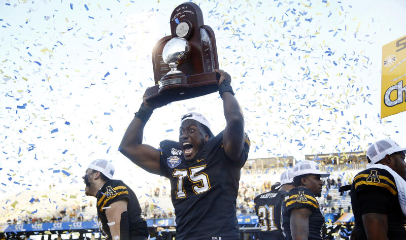 Appalachian State offensive lineman Victor Johnson (75) celebrates with the trophy following their 45-38 win over Louisiana-Lafayette in an NCAA college football game for the Sun Belt Football Championship on Saturday, Dec. 7, 2019, in Boone, N.C. (AP Photo/Brian Blanco)