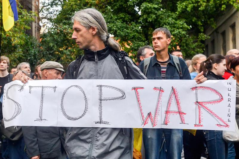 "A protester holds a placard reading ""Stop war in Ukraine"" during a rally outside the Russian Consulate in the southeastern Ukrainian city of Kharkiv on August 28, 2014"