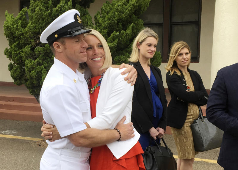 FILE - In this Thursday, May 30, 2019, file photo, U.S. Navy Special Operations Chief Edward Gallagher, left, hugs his wife, Andrea Gallagher, after leaving a military courtroom on Naval Base San Diego, in San Diego. Edward Gallagher, who has been charged with allegedly killing an Islamic State prisoner in his care and attempted murder for the shootings of two Iraq civilians in 2017, is scheduled to go on trial Monday, June 17, 2019. (AP Photo/Julie Watson, File)
