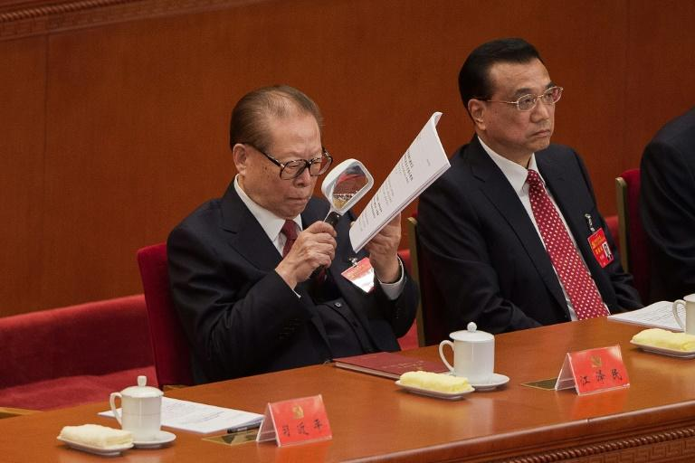 China's former president Jiang Zemin, sitting next to Premier Li Keqiang (R), reads papers with a magnifying glass as he listens to President Xi Jinping's address at the opening of the 19th Communist Party Congress