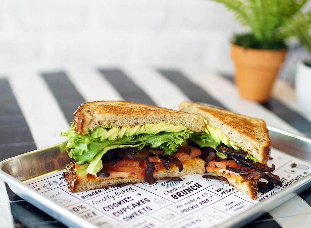 """by Chloe's burgers are known as some of the best in the vegan foodie world, but if you're not looking to splurge on lunch, then one of the sandwiches is a better option. """"The 'Burg BLT is the best choice if your eyes are set on the burgers or sandwiches. It has the simplest ingredients out of the available options and uses 7-grain toast, which is packed with B vitamins, <a rel=""""nofollow"""" href=""""https://www.eatthis.com/iron-rich-foods/?utm_source=yahoo-news&utm_medium=feed&utm_campaign=yahoo-feed"""">iron</a> and folate,"""" Beckerman says. If you want to cut back on the calories, you can still enjoy the sandwich, but with one simple tweak. """"I would recommend using half the bun (or toast). You can save 80 calories if you enjoy it open-faced, and you won't fill your belly with rapidly digesting carbohydrates that can cause fatigue and irritability,"""" Beckerman says."""