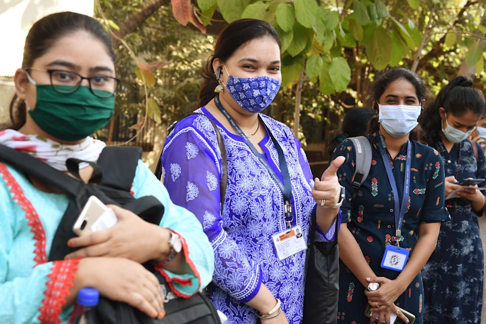 A health worker gives a thumbs-up gesture as she waits in line to receive a dose of a Covid-19 coronavirus vaccine at the Cooper hospital in Mumbai on January 16, 2021. (Photo by Punit PARANJPE / AFP) (Photo by PUNIT PARANJPE/AFP via Getty Images)