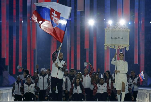 Slovakia's flag-bearer Jakub Krako (C), leads his country's contingent during the opening ceremony of the 2014 Paralympic Winter Games in Sochi, March 7, 2014. REUTERS/Alexander Demianchuk (RUSSIA - Tags: OLYMPICS SPORT)