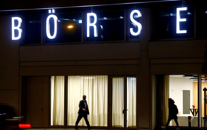 "FILE PHOTO: A man walks under the illuminated word ""Borse"" as he passes the headquarters of Swiss stock exchange operator SIX Group in Zurich"