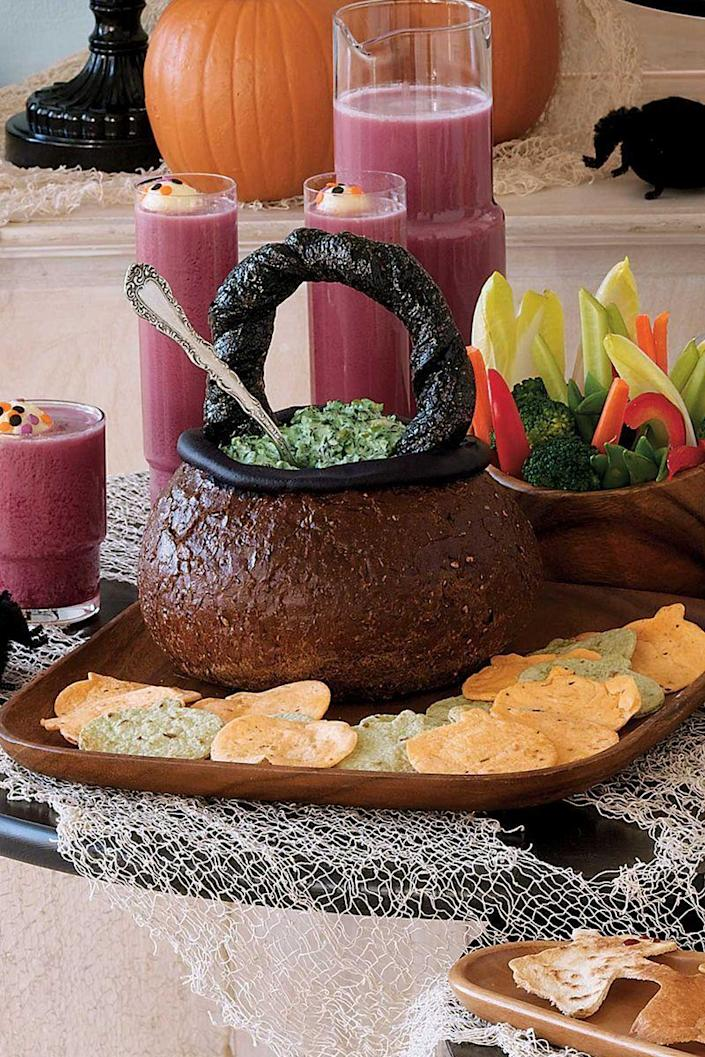 """<p>Impress guests with this crafty Halloween appetizer, which cleverly transforms pumpernickel bread, breadsticks, and cream cheese into a basket, then fill it with a super-simple creamy spinach dip.</p><p><em><strong><a href=""""https://www.womansday.com/food-recipes/food-drinks/recipes/a10930/spooky-spinach-dip-in-bread-bowl-cauldron-recipe-122179/"""" rel=""""nofollow noopener"""" target=""""_blank"""" data-ylk=""""slk:Get the Spooky Spinach Dip in a Cauldron Bread Bowl recipe."""" class=""""link rapid-noclick-resp"""">Get the Spooky Spinach Dip in a Cauldron Bread Bowl recipe.</a></strong></em></p>"""