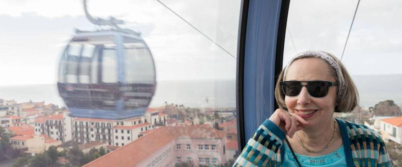 Smiling female tourist in cable car over the city of Funchal in Madiera