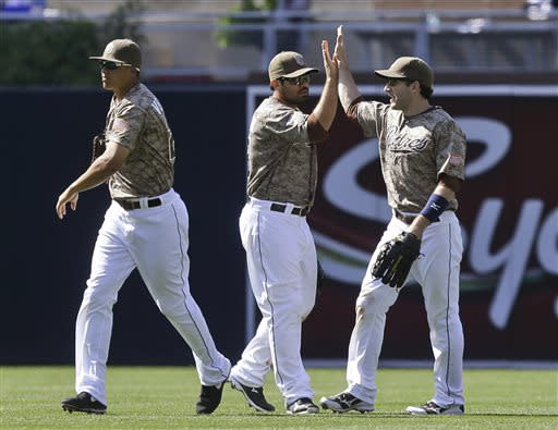 The San Diego Padres outfield of Will Venable, left, Carlos Quentin, center, and Chris Denorfia, all of whom homered in the game, high-five after the Padres' 10-1 victory over the San Francisco Giants in a baseball game in San Diego, Sunday, July 14, 2013. (AP Photo/Lenny Ignelzi)
