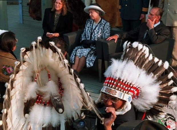 Chief Eric Large of the Saddle Lake First Nation in Alberta checks his video camera as the royal couple, accompanied by N.W.T. Premier Nellie Cournoyea, attend a traditional and cultural demonstration in Yellowknife on Aug. 21, 1994.