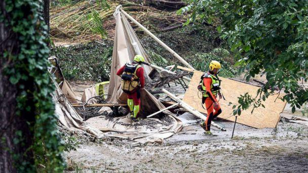 PHOTO: Rescuers walk past a damaged tent in a flooded camping as storms and heavy rains sweep across France, Aug. 9, 2018, in Saint-Julien-de-Peyrolas, southern France. (Boris Horvat/AFP/Getty Images)