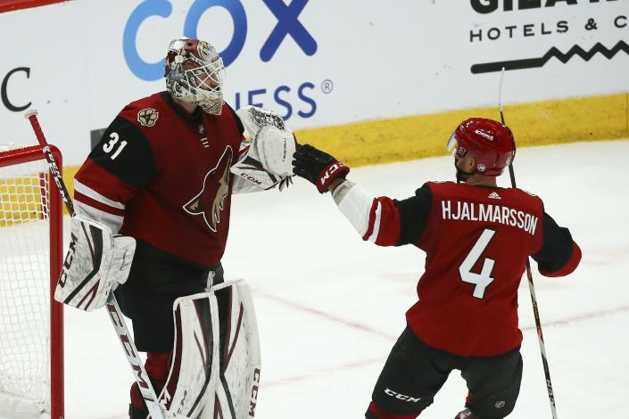 Arizona Coyotes goaltender Adin Hill (31) celebrates a win against the San Jose Sharks with Coyotes defenseman Niklas Hjalmarsson (4) as time expires in the third period of an NHL hockey game Tuesday, Jan. 14, 2020, in Glendale, Ariz. The Coyotes defeated the Sharks 6-3. (AP Photo/Ross D. Franklin)