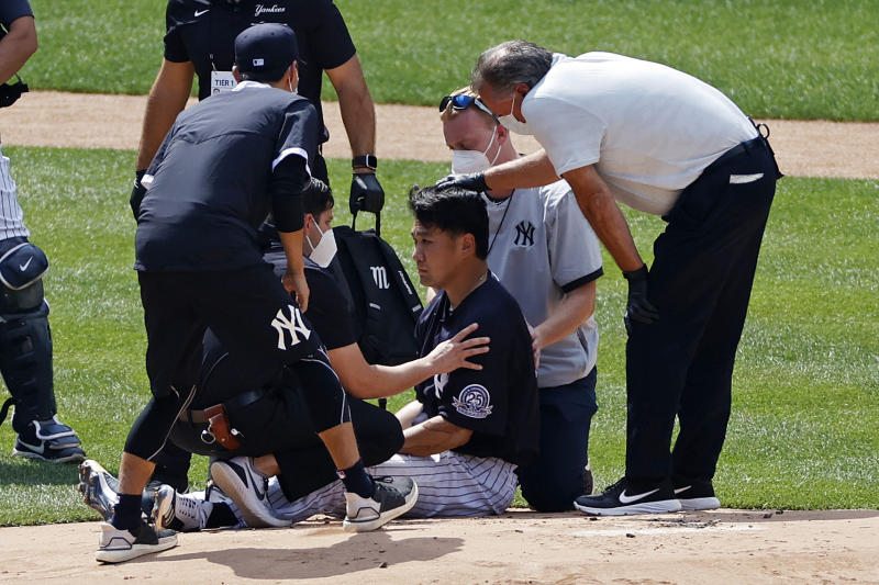 New York Yankees pitcher Masahiro Tanaka is tended to by team medical personnel after being hit by a ball off the bat of Yankees Giancarlo Stanton during a baseball a workout at Yankee Stadium in New York, Saturday, July 4, 2020. (AP Photo/Adam Hunger)