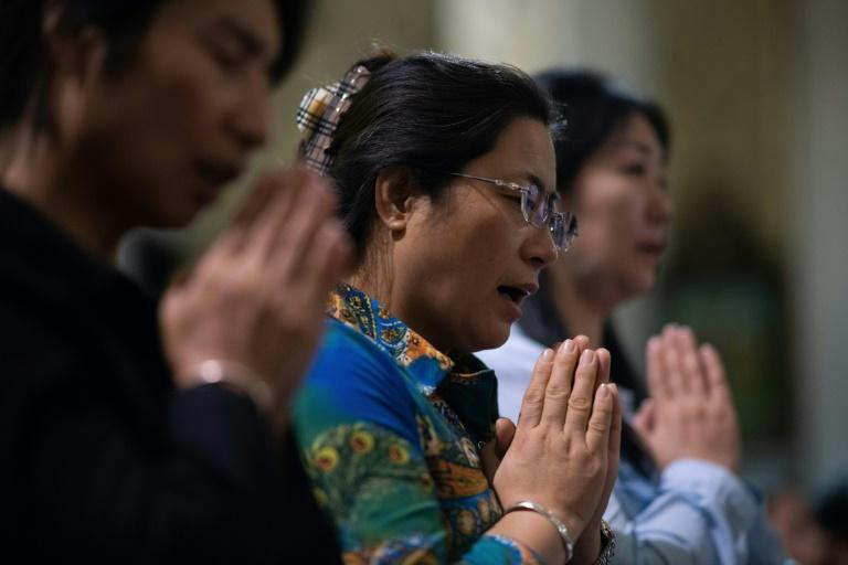 Christian devotees pray during a mass at the South Cathedral in Beijing