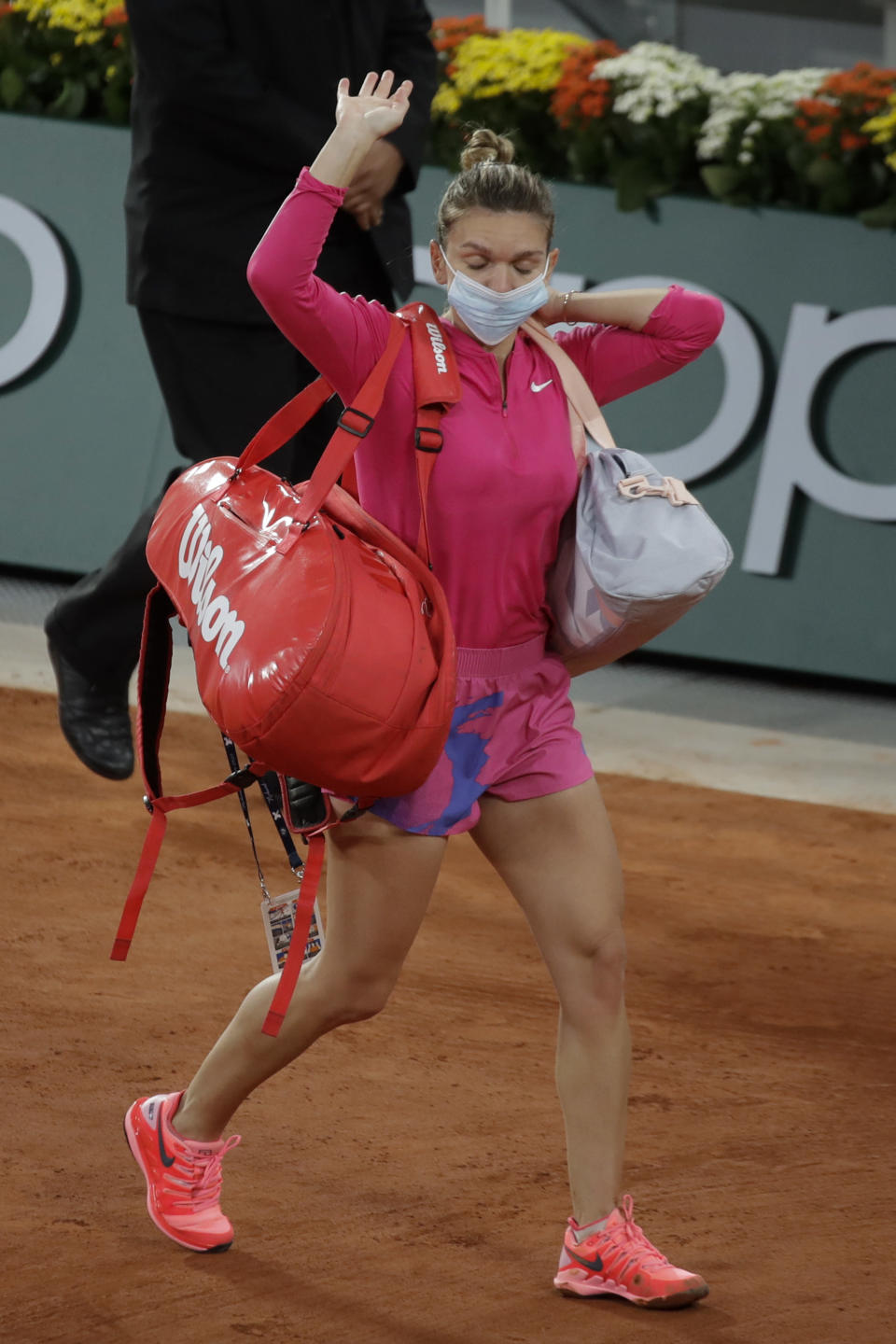 FILE - In this file photo dated Sunday, Oct. 4, 2020, Romania's Simona Halep wears a face mask as she leaves after losing her fourth round match of the French Open tennis tournament against Poland's Iga Swiatek at the Roland Garros stadium in Paris, France. Simona Halep said Saturday Oct. 31, 2020, that she has tested positive for COVID-19 coronavirus. (AP Photo/Alessandra Tarantino, FILE)