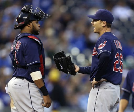 Cleveland Indians catcher Carlos Santana, left, talks with starting pitcher Scott Kazmir during the fifth inning of a baseball game against the Kansas City Royals Saturday, April 27, 2013, in Kansas City, Mo. (AP Photo/Ed Zurga)