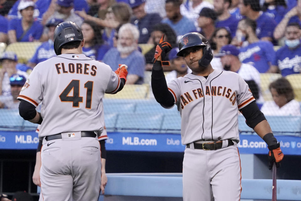 San Francisco Giants' Wilmer Flores, left, celebrates his solo home run with Donovan Solano during the first inning of a baseball game Monday, July 19, 2021, in Los Angeles. (AP Photo/Mark J. Terrill)