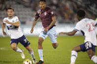 Colorado Rapids midfielder Mark-Anthony Kaye, center, drives with the ball between Vancouver Whitecaps midfielder Russell Teibert, left, and defender Javain Brown in the first half of an MLS soccer match Sunday, Sept. 19, 2021, in Commerce City, Colo. (AP Photo/David Zalubowski)