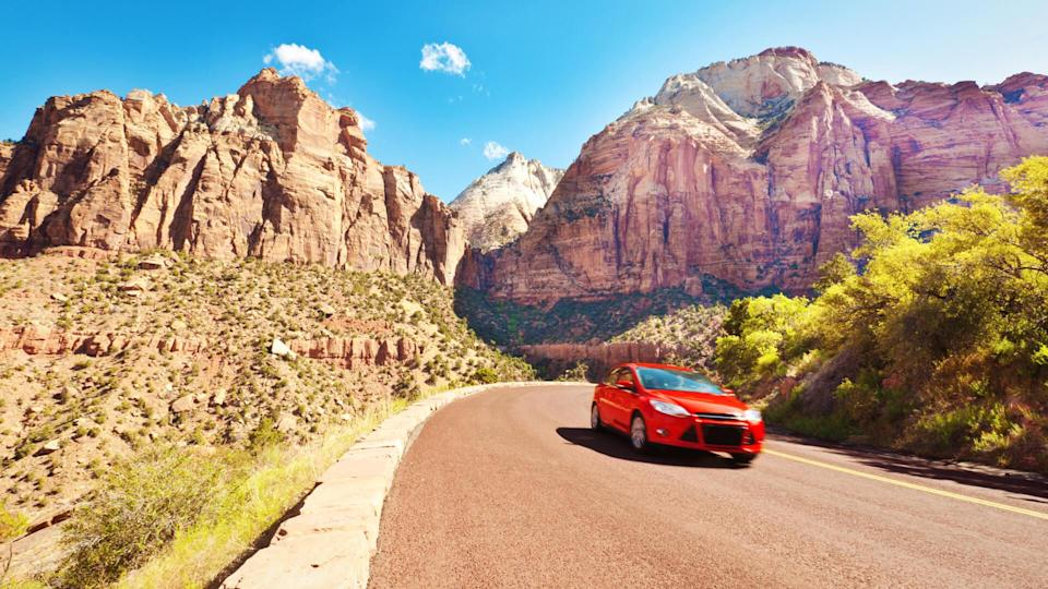 A red car vehicle touring the scenic mountain highways.