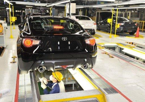 This file photo shows a worker checking out a car body at a plant in Ota-city, Gunma prefecture, in March. Japan's factory output turned down unexpectedly last month, according to official data released on Monday, stoking concerns that turmoil overseas is damaging recovery in the world's third-largest economy