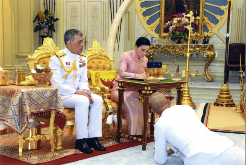 In this photo released by Bureau of the Royal Household ,Thailand's King Maha Vajiralongkorn Bodindradebayavarangkun, left, sits with Queen Suthida Vajiralongkorn Na Ayudhya as they sign their marriage certificates at Ampornsan Throne Hall in Bangkok, Thailand, Wednesday, May 1, 2019.Thailand's King Maha Vajiralongkorn, who will have his official coronation on Saturday, has appointed his consort as the country's queen. An announcement Wednesday in the Royal Gazette said Suthida Vajiralongkorn Na Ayudhya is legally married to the 66-year-old king, and is now Queen Suthida. (Bureau of the Royal Household via AP)