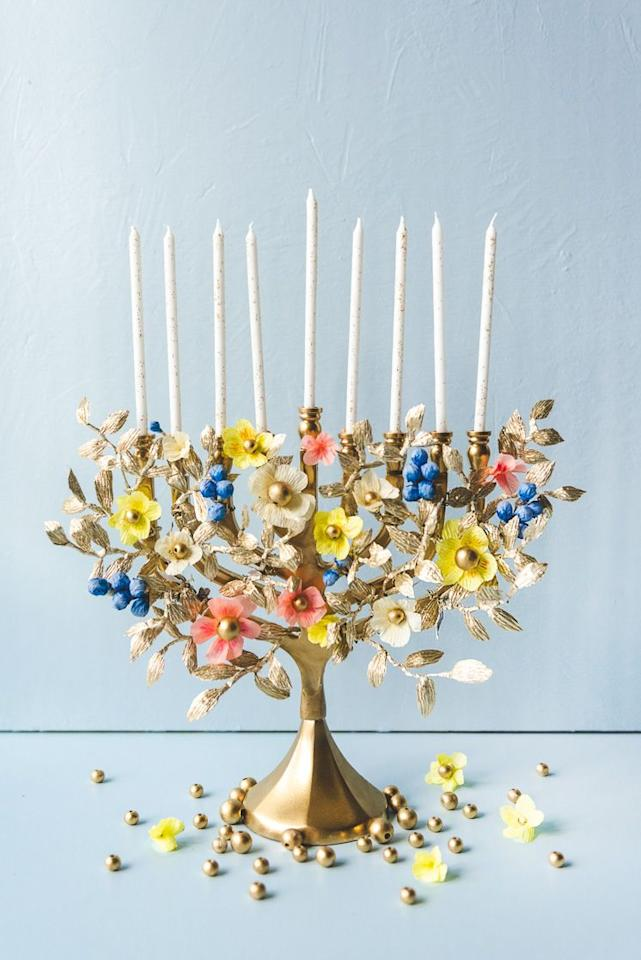 """<p>Start with a store-bought menorah and transform it into a museum-worthy work of art with this advanced project. Paint the menorah gold and wrap it with handmade paper flowers for a striking result.</p><p><em><a href=""""https://thehousethatlarsbuilt.com/2019/12/diy-paper-flower-menorah.html/"""" target=""""_blank"""">Get the tutorial at The House That Lars Built</a></em></p>"""