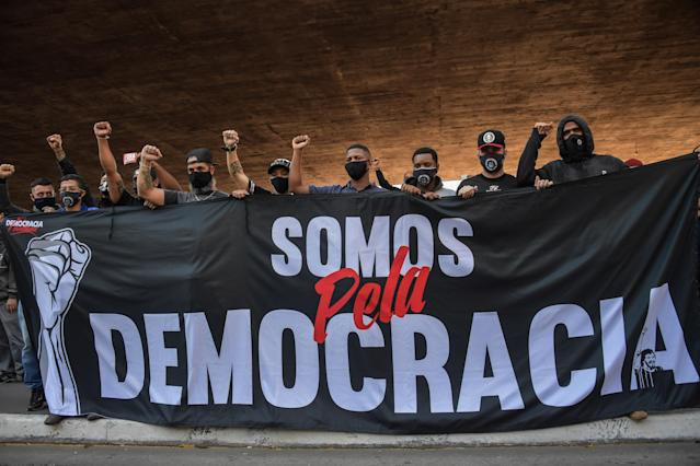 """TOPSHOT - Anti-Brazilian President Jair Bolsonaro football fans protest against him with a banner reading """"We are for democracy"""" at Paulista Avenue in Sao Paulo, Brazil, on May 31, 2020, amid the COVID-19 novel coronavirus pandemic. (Photo by NELSON ALMEIDA / AFP) (Photo by NELSON ALMEIDA/AFP via Getty Images)"""