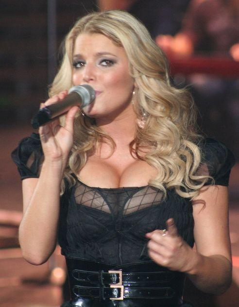 Jessica Simpson looks dazzling during a stage performance as she holds a microphone to her mouth.