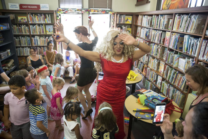 Vanessa Carr, right, and Blazen Haven singalong with children 'The Hokey Pokey,' during Drag Queen Story Time at the Alvar Library in New Orleans on Saturday, Aug. 25, 2018. Children and parents and caregivers packed into the library to hear stories and sing songs during the event. (Scott Threlkeld/The Advocate via AP)