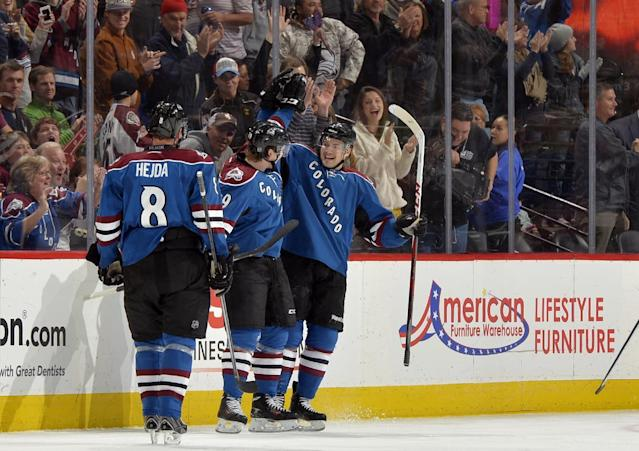 Colorado Avalanche center Nathan MacKinnon, center, is congratulated by teammates John Mitchell (7) and Jan Hejda (8) after scoring a goal against the Minnesota Wild during the second period of an NHL hockey game on Saturday, Nov. 30, 2013, in Denver. (AP Photo/Jack Dempsey)