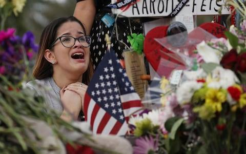 Ariana Gonzalez is over come with emotion as she visits a cross setup for her friend, football coach Aaron Feis, at the memorial in front of Marjory Stoneman Douglas High School  - Credit: Joe Raedle/Getty