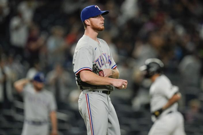 Texas Rangers starting pitcher A.J. Alexy, foreground, reacts as New York Yankees' Gary Sanchez runs the bases after hitting a home run during the second inning of a baseball game Monday, Sept. 20, 2021, in New York. (AP Photo/Frank Franklin II)