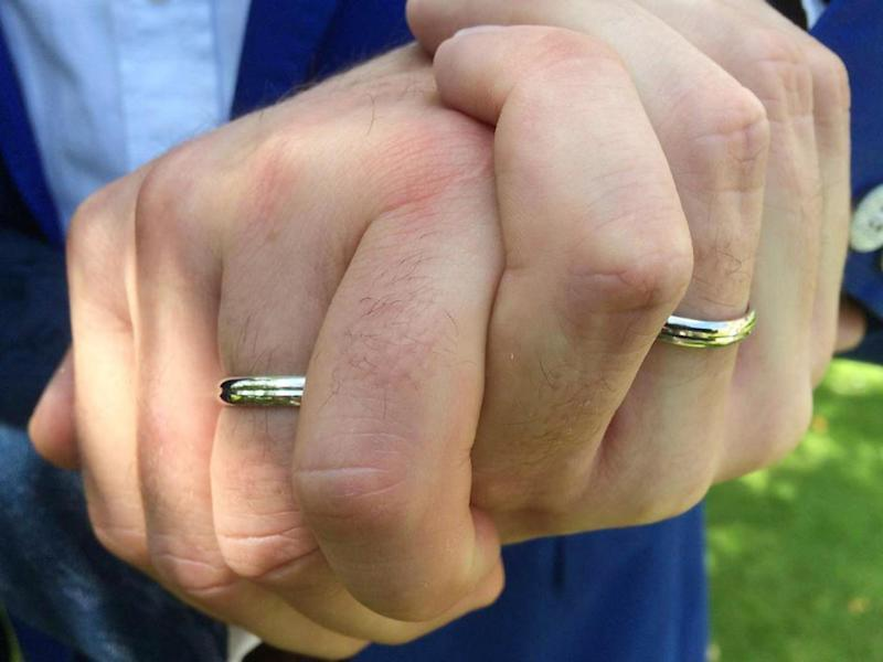 The two men show off their rings at their wedding, which is not officially recognised by the Church of England