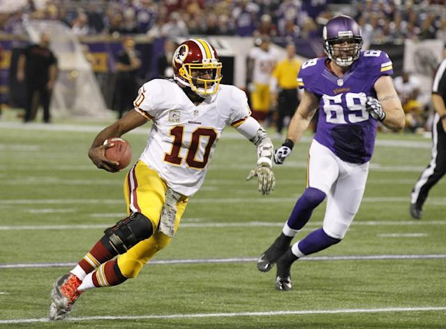 Washington Redskins quarterback Robert Griffin III runs from Minnesota Vikings defensive end Jared Allen (69) during the first half of an NFL football game, Thursday, Nov. 7, 2013, in Minneapolis. (AP Photo/Ann Heisenfelt)