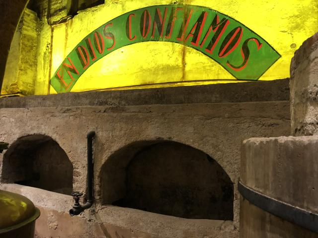 "This historic distillery produced Herradura tequila from 1870 to 1963, when the facility's modern operation was built next door. The words ""En Dios Confiamos"" emblazoned on the wall where workers once toiled to ferment and distill tequila mean ""In God We Trust."" [Photo: Mary Ann Akers]"