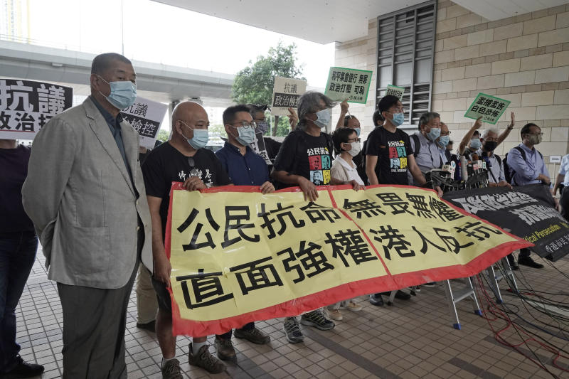 "Hong Kong businessman and media tycoon Jimmy Lai, left, and other pro-democracy activists hold a banner after arriving at a court in Hong Kong, Friday, Sept. 18, 2020. Pro-democracy activists including Lai, former lawmakers Martin Lee and Lee Cheuk-yan were among of 15 pro-democracy activists appeared in court for charges of participating and organizing anti-government protests last year. The banner reads ""Civil disobedience, fearless and invincible, facing autocracy, Hong Kong people rebellion."" (AP Photo/Kin Cheung)"