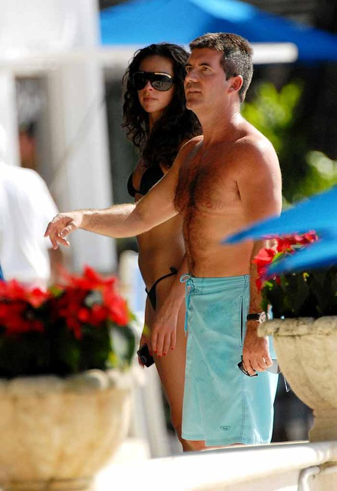 """American Idol"" judge Simon Cowell and his girlfriend Teri Seymour worked on their tans in Barbados. Why the grumpy face Simon? You're supposed to be on vacay! <a href=""http://www.splashnewsonline.com/"" target=""new"">Splash News</a> - December 27, 2007"