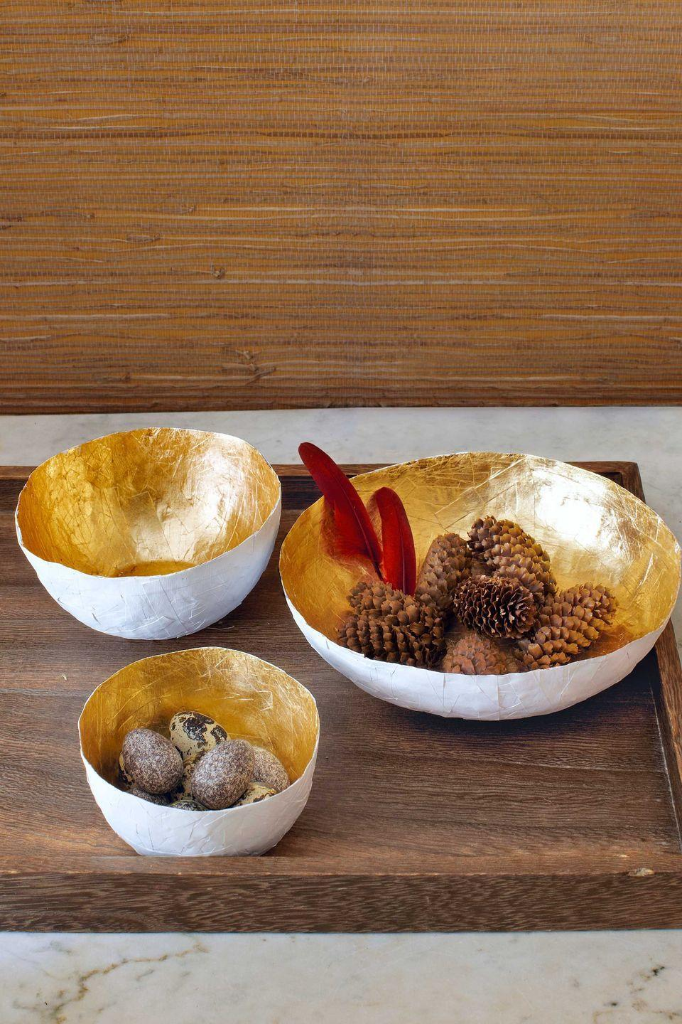 <p>Upcycle shredded paper into a set of gilded decorative bowls. First, choose a bowl (or multiple different-size bowls) to use as a mold. For each container you plan to create, follow these steps:</p><p><strong>Step 1:</strong> Tightly cover the outside of your bowl with plastic wrap, securing it on the inside with painter's tape, and turn upside down. In another bowl, mix equal parts Elmer's white school glue and water. Dip shredded paper into the mixture, evenly coating each piece; then lay the strips atop the plastic-wrapped bowl so they overlap, until the bowl's exterior is completely covered. Let dry for three hours.</p><p><strong>Step 2:</strong> Flip the bowl right side up and trim away any excess paper along the rim with scissors. Then, loosen and separate your paper bowl from the plastic-wrapped bowl.</p><p><strong>Step 3:</strong> Paint the interior of your paper bowl with white acrylic paint and let it dry for one hour; then paint the exterior and let it dry for an hour.</p><p><strong>Step 4:</strong> Cover the outside of your paper bowl with wax paper, securing it to the bowl's outer rim with painter's tape. Next, apply gold leaf to the bowl's interior. Follow the package instructions, and let set overnight.</p><p><strong>Step 5: </strong>Apply neutral-toned Liberon Wax to the interior of the bowl with a soft cloth. Allow the wax to set for an hour, then gently buff to a shine with a clean soft cloth. Finally, remove the tape and wax paper, and display a few treasures in your lustrous vessel.</p>