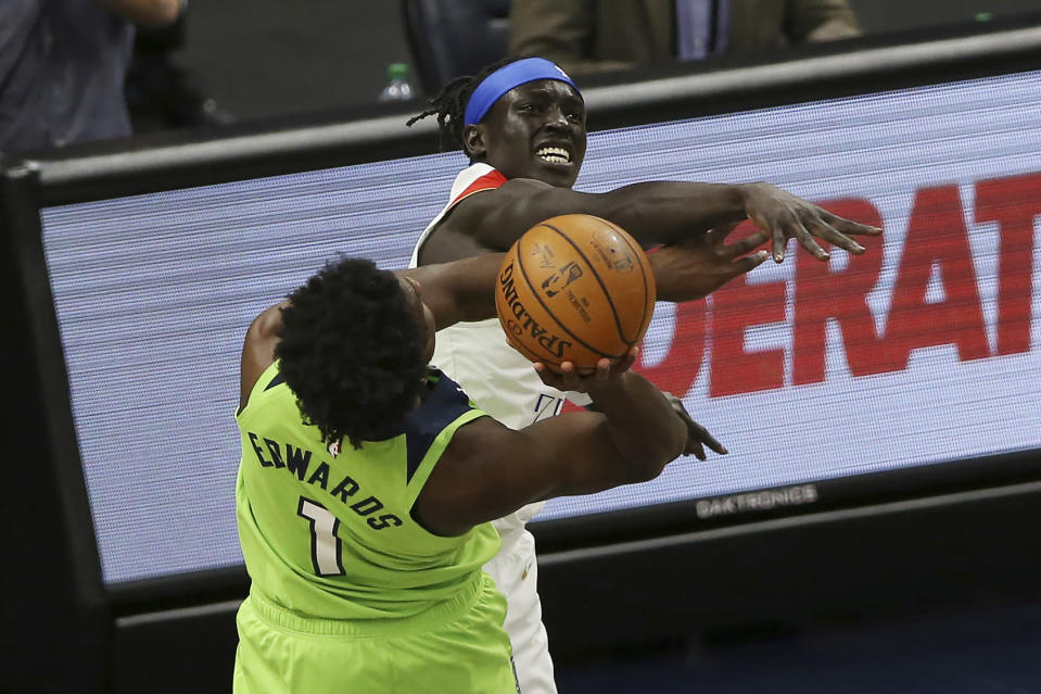 Minnesota Timberwolves' Anthony Edwards (1) is fouled by New Orleans Pelicans' Wenyen Gabriel (32) while trying to shoot during the first half of an NBA basketball game Saturday, May 1, 2021, in Minneapolis. (AP Photo/Stacy Bengs)