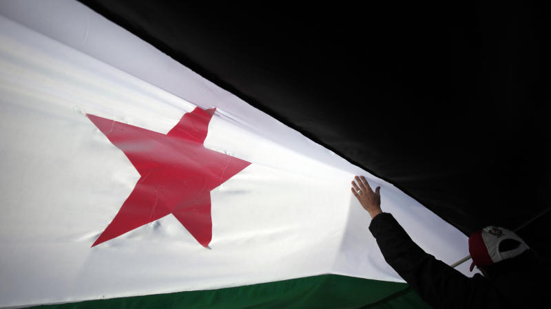 A protester walks under a revolutionary Syrian flag during a rally against the regime of Syrian President Bashar al-Assad in front of the Syrian embassy in Sofia, Bulgaria, on Sunday, Nov. 27, 2011.  More than 3,500 people have died in months of anti-government protests in Syria, according to the UN. (AP Photo/Valentina Petrova)
