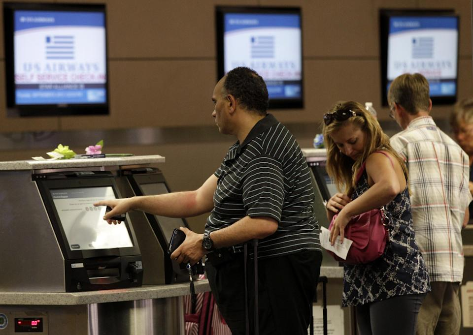 In this Sept. 6, 2012, file photo, passengers use the self service check-in at the U.S. Airways gate at Dallas-Fort Worth International Airport, in Grapevine, Texas. According to a three-month AP investigation released in January 2013, five years after the start of the Great Recession, instead of relying on someone else in the workplace or their personal lives, people are using technology to do tasks independently. (AP Photo/Tony Gutierrez)