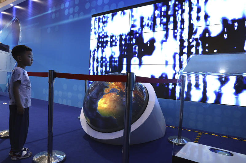 """A child watches a video depicting the flow of digital information during the National Science and Technology Week exhibition held at the Military Museum in Beijing on Friday, May 24, 2019. Stepping up Beijing's propaganda offensive in the tariffs standoff with Washington, Chinese state media on Friday accused the U.S. of seeking to """"colonize global business"""" with moves against Huawei and other Chinese technology companies. (AP Photos/Ng Han Guan)"""
