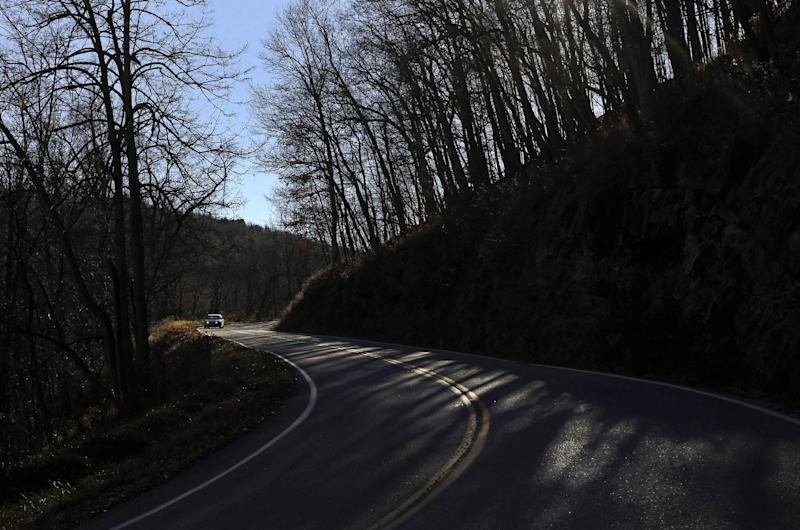 In this Nov. 13, 2013 photo, sunlight peaks through trees as a car winds down a mountain road in Highland County, Va., inside the National Radio Quiet Zone. The 13,000 square-mile quiet zone -- larger than the state of Maryland -- protects a sensitive radio astronomy facility located just over the border in Pocahontas County, W.Va., as well as a nearby Naval research facility, from interference created by cell phones and other everyday devices that emit electromagnetic waves. (AP Photo/Patrick Semansky)