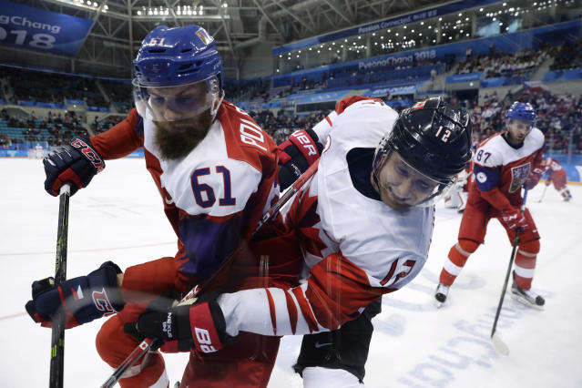Adam Polasek (61), of the Czech Republic, and Rob Klinkhammer (12), of Canada, battle for the puck during the third period of the men's bronze medal hockey game at the 2018 Winter Olympics in Gangneung, South Korea, Saturday, Feb. 24, 2018. (AP Photo/Matt Slocum)