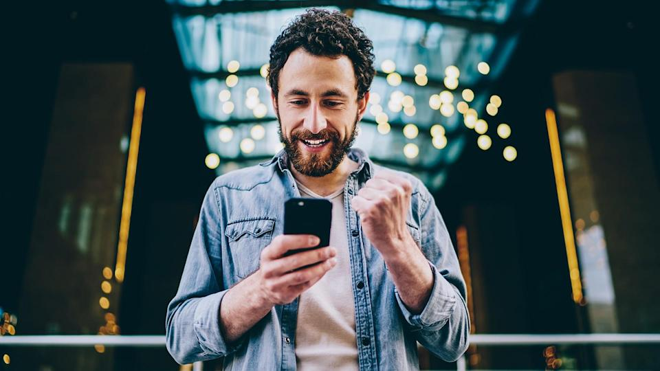 Excited bearded young man blogger cheering favourite team during live stream on website on modern smartphone.