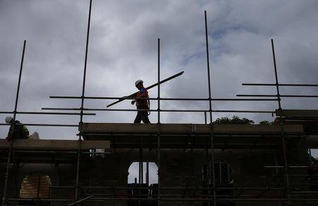 A builder assembles scaffolding as he works on new homes being built for private sale on a council housing estate, in south London