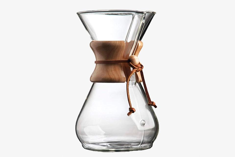 """It's a classic for a reason: The Chemex pour-over is simple to use and yields smooth, delicious coffee with every brew. A paper filter with coffee grounds goes right into the top cone, followed by boiling water. This eight-cup version is a solid foundation for any <a href=""""https://www.cntraveler.com/story/best-travel-gifts-under-100-dollars?mbid=synd_yahoo_rss"""" rel=""""nofollow noopener"""" target=""""_blank"""" data-ylk=""""slk:at-home"""" class=""""link rapid-noclick-resp"""">at-home</a> morning coffee ritual, and Chemex even says that the minimalist hourglass design allows for coffee to be covered, refrigerated, and reheated without losing any of flavor. $47, Amazon. <a href=""""https://www.amazon.com/Chemex-Classic-Pour-over-Glass-Coffeemaker/dp/B000I1WP7W"""" rel=""""nofollow noopener"""" target=""""_blank"""" data-ylk=""""slk:Get it now!"""" class=""""link rapid-noclick-resp"""">Get it now!</a>"""
